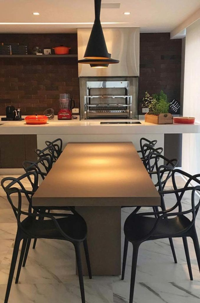 Varanda gourmet elétrica e mesa moderna.