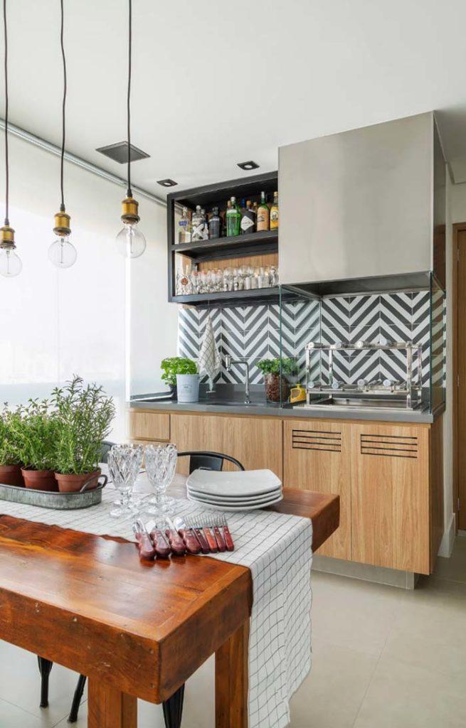 Varanda gourmet com azulejo decorado e churrasqueira de vidro.