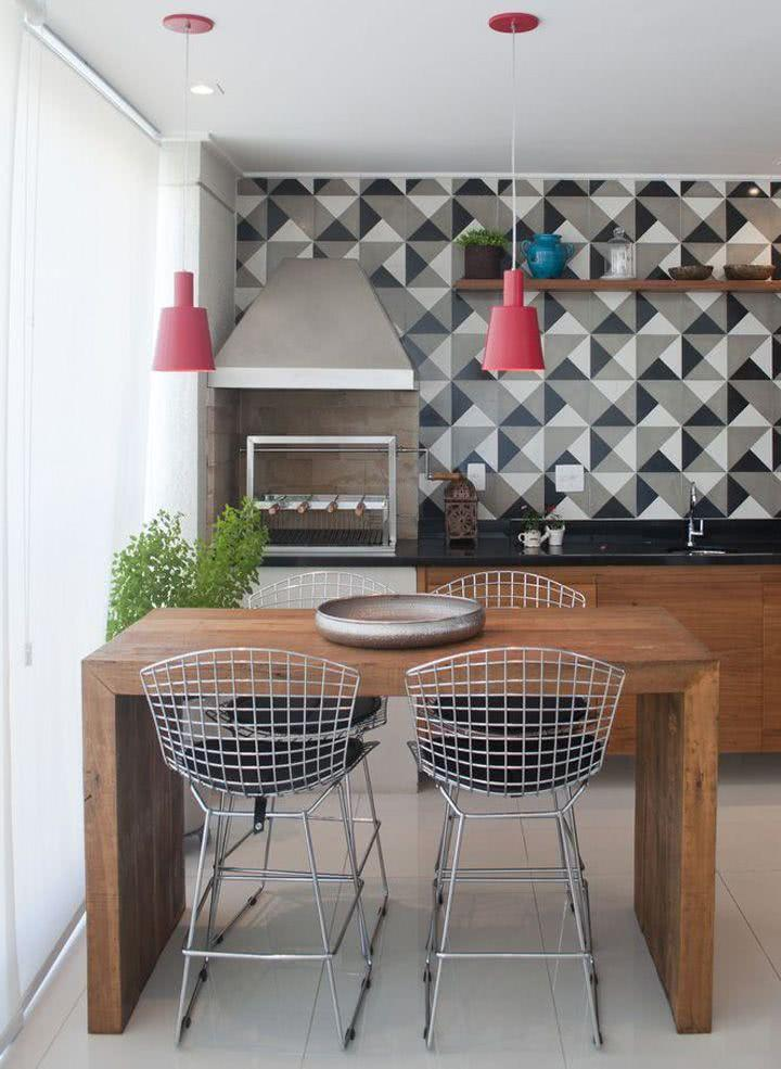 Varanda gourmet com bancada de madeira e azulejo moderno.