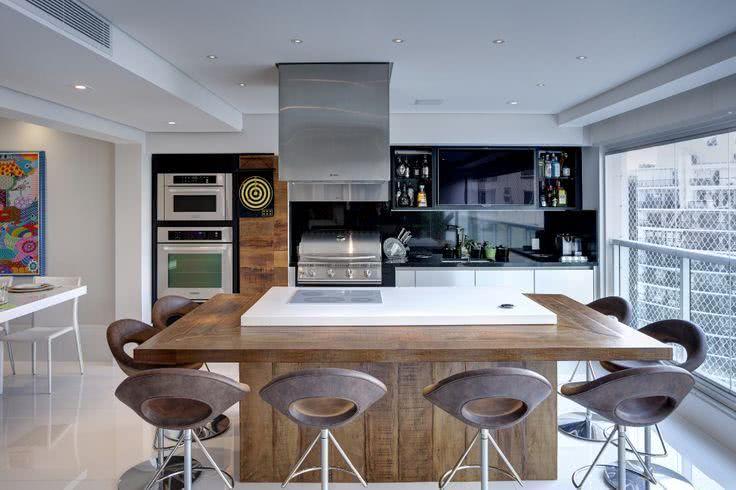 Cozinha externa com ilha e churrasqueira a bafo.