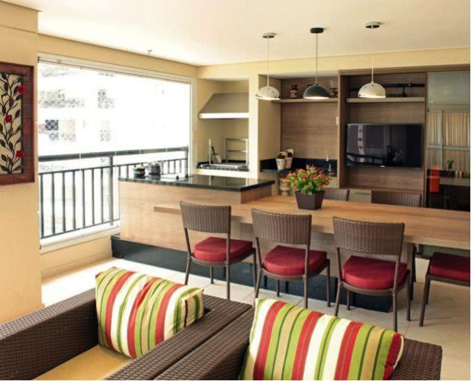Área externa com bancada de madeira e móveis de vime.