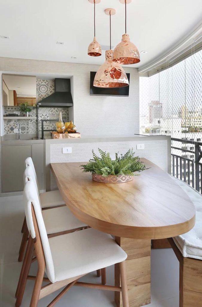 Cozinha externa com pendente suspenso de cobre.