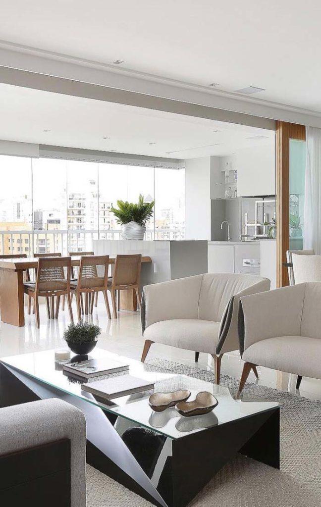 Cozinha externa com mesa de madeira e bancada de porcelanato.