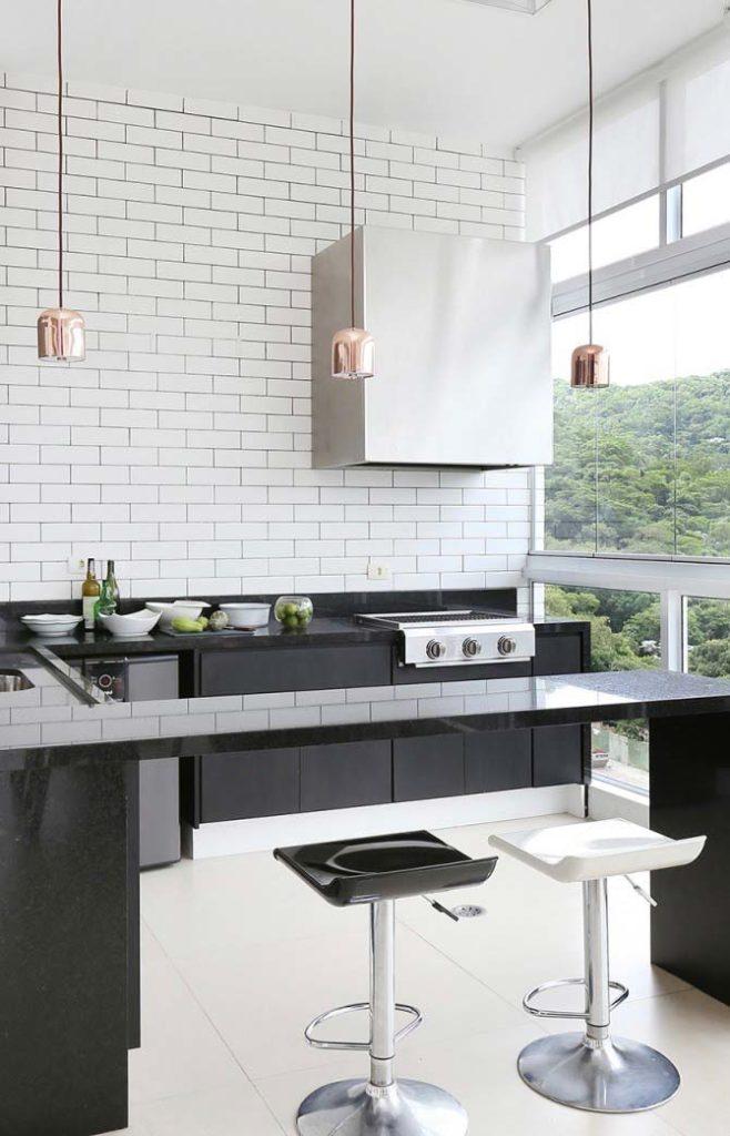 Cozinha externa com azulejo metro white e bancada de granito.