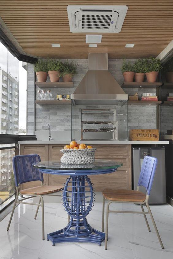 Cozinha externa com churrasqueira de vidro.