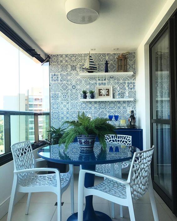 Cozinha externa com mesa azul e azulejo português.