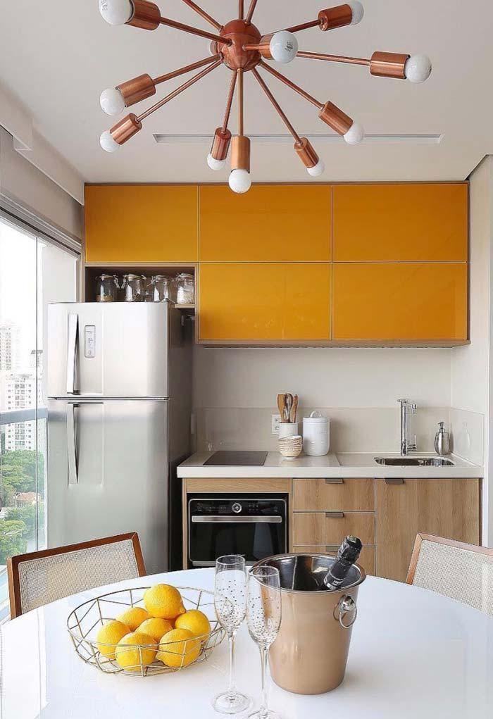 Cozinha externa com armário laranja e cooktop.