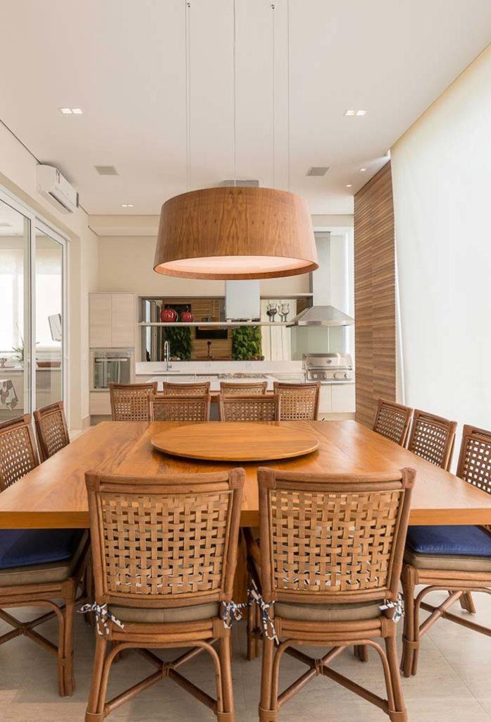 Cozinha externa com mesa de madeira grande e churrasqueira a bafo.