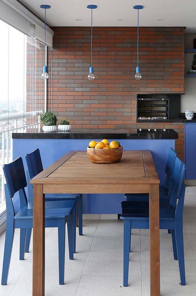Cozinha externa com mesa de madeira com azulejo de tijolinho e churrasqueira.