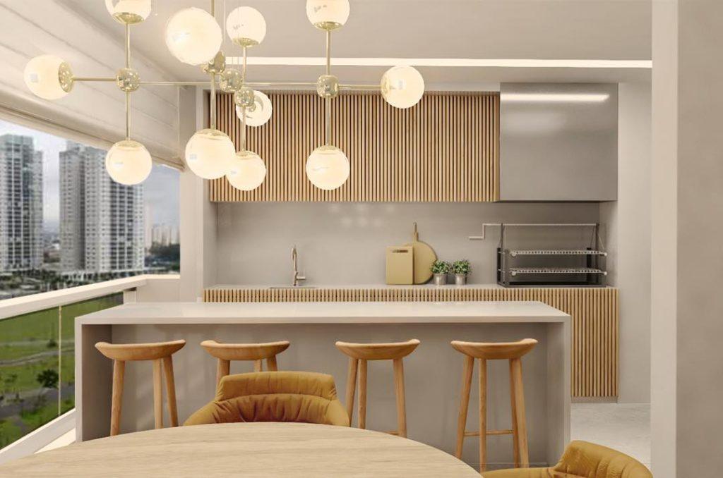 Varanda gourmet com decoração luxuosa, churrasqueira elétrica e lustre moderno.