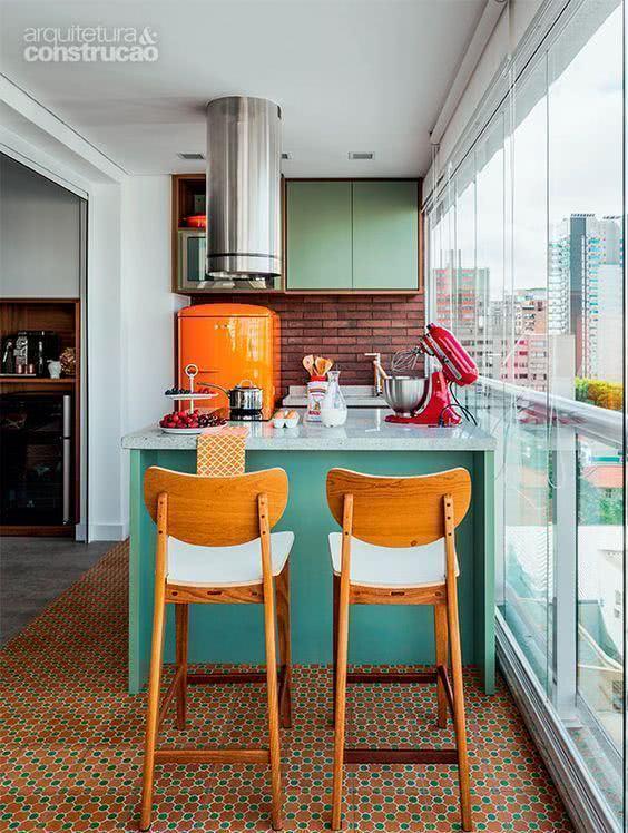 Varanda gourmet pequena com decoração colorida e azulejo de tijolinho.