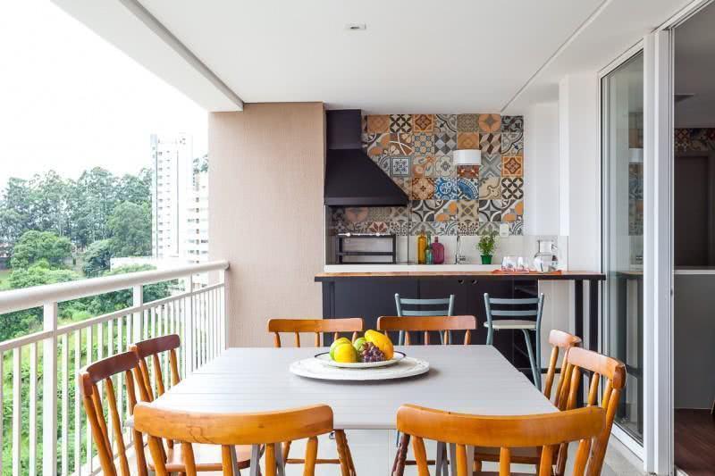 Cozinha externa com churrasqueira de vidro e azulejo decorado.