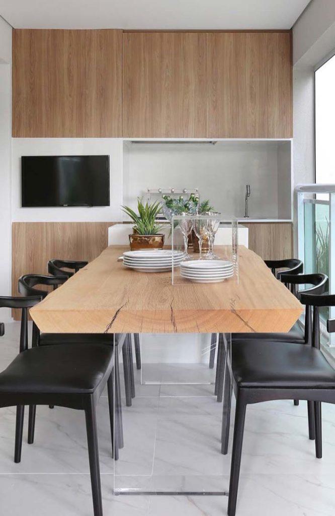 Cozinha externa com mesa rústica e armário de madeira.