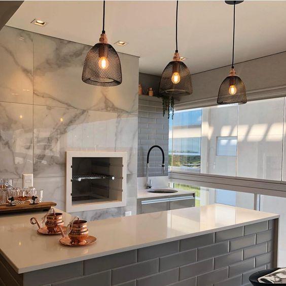 Cozinha externo com bancada de azulejo de tijolinho azul e pendente suspenso.
