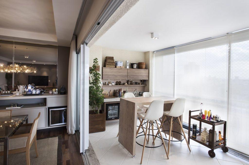 Cozinha externa com bancada de madeira e minibar.
