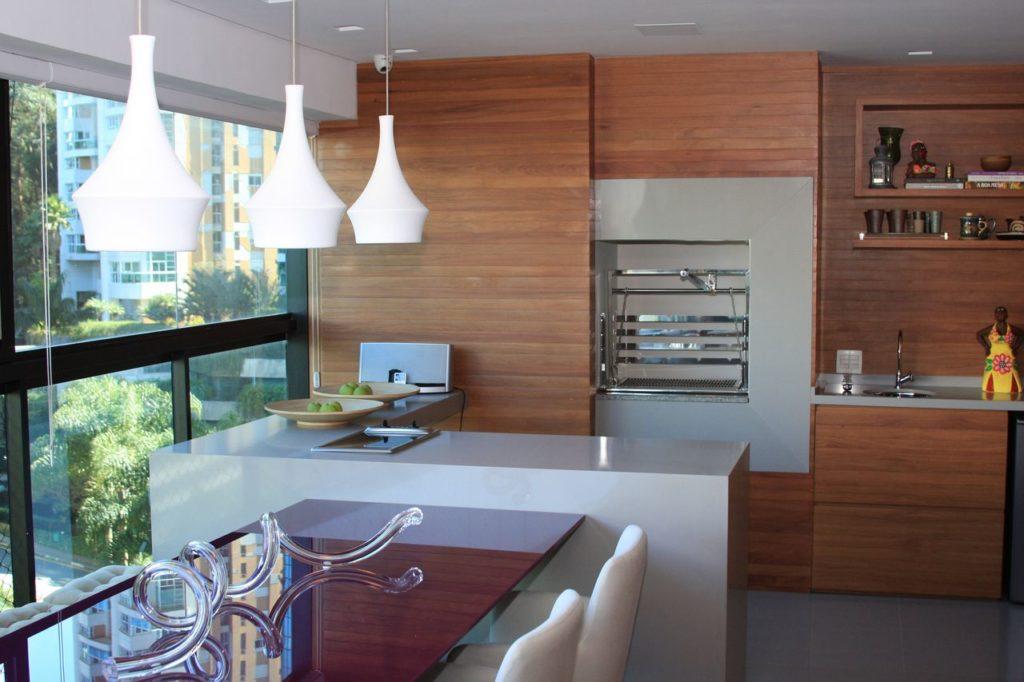 Cozinha externa com churrasqueira elétrica e bancada de porcelanato.