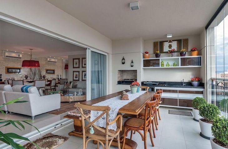 Cozinha externa com mesa rústica e churrasqueira.