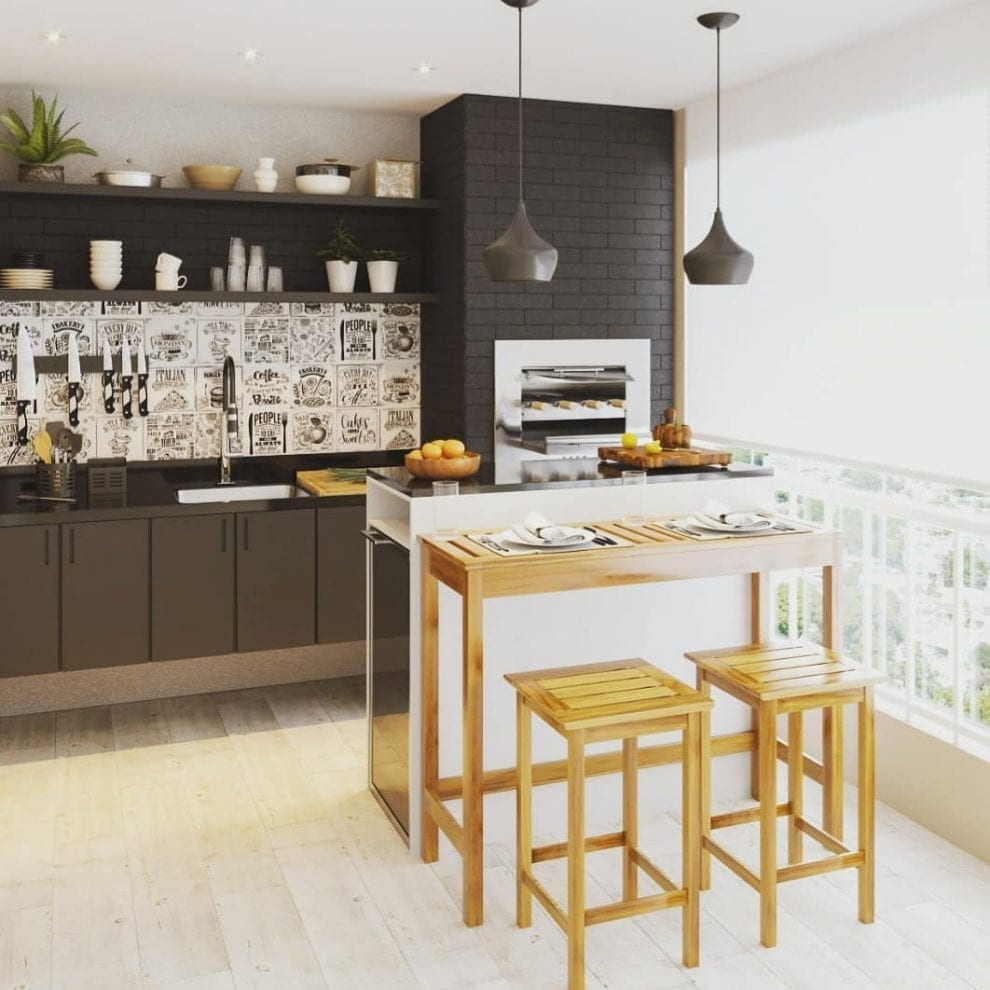 Cozinha externa com armário preto e mesa de madeira.