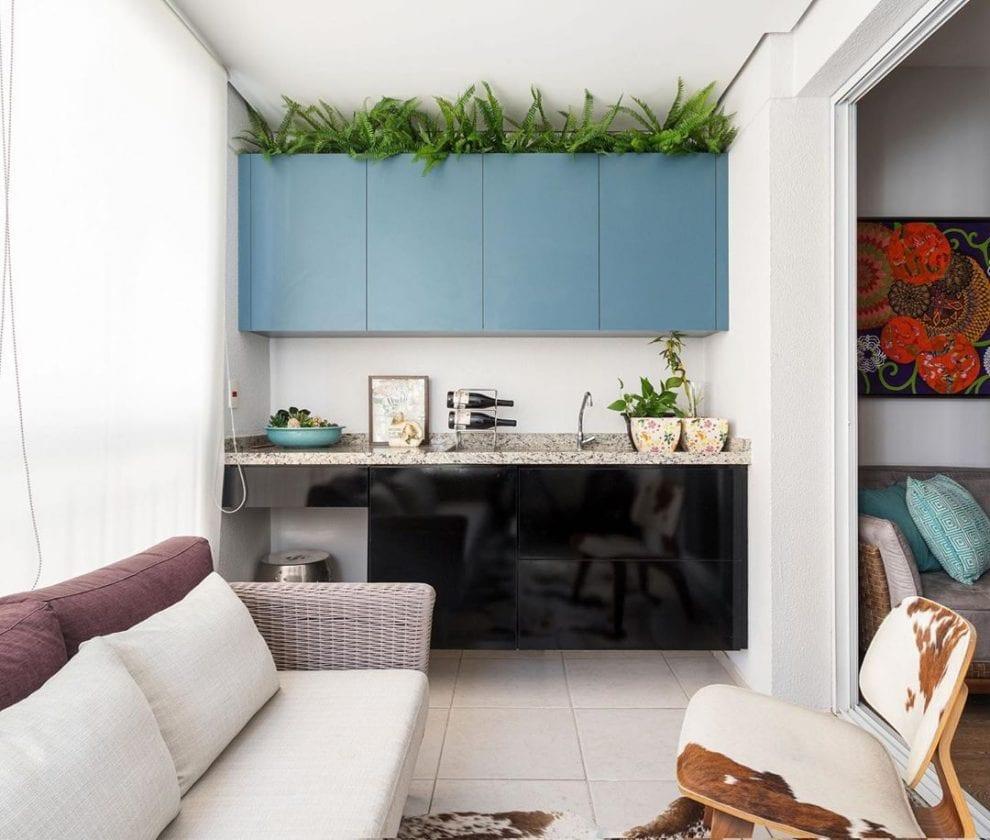 Cozinha externa com armário colorido e sofá de vime.