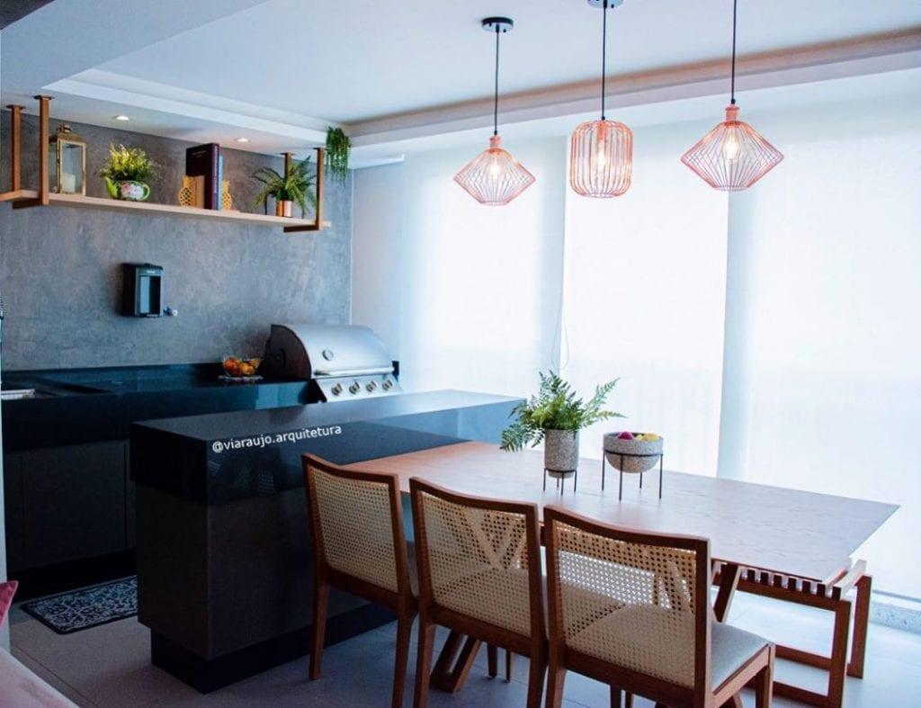 Cozinha externa com pendentes suspensos e bancada de granito.