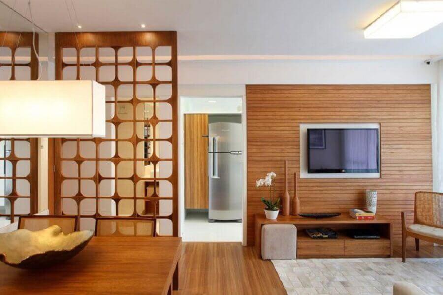 Sala decorada com divisória de ambiente de madeira vazada.