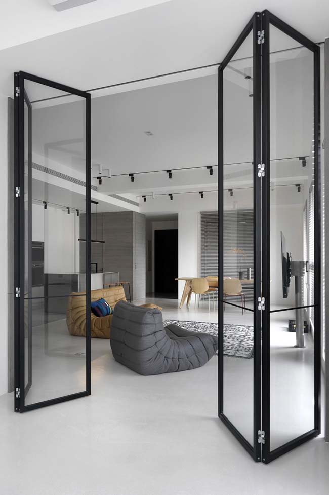 Sala moderna com divisória de ambiente de biombo de vidro.