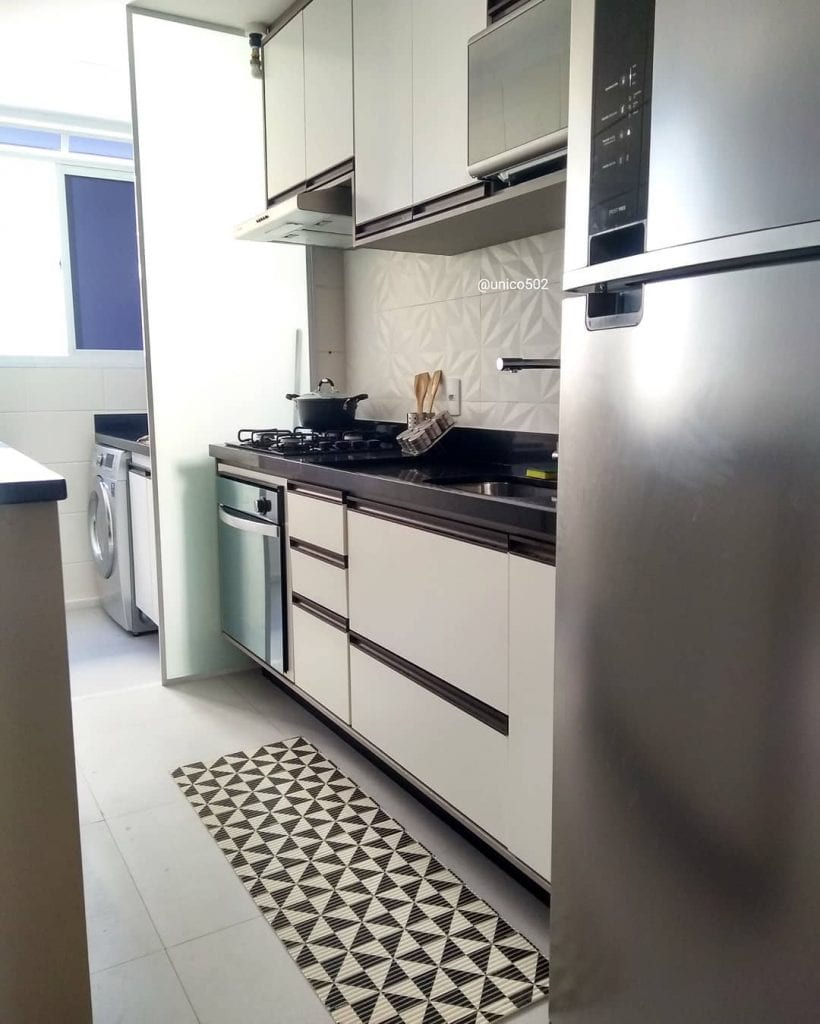 Cozinha pequena com divisória de ambiente de vidro.