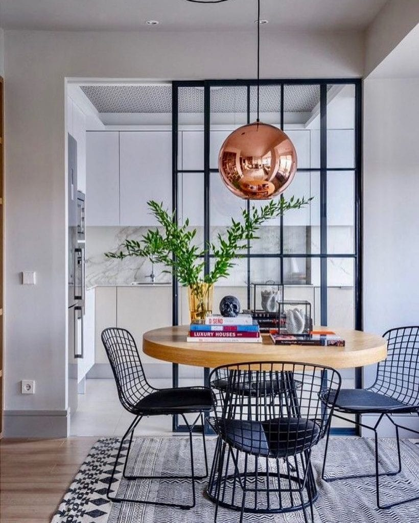 Cozinha em L minimalista com divisória de ambiente de vidro.