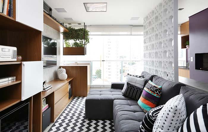 Sala pequena com divisória de ambiente de cobogó branco.