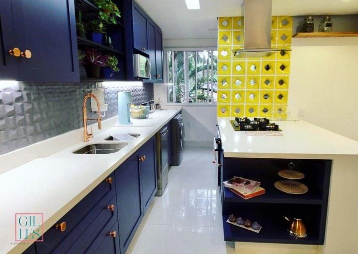 Cozinha americana com armários azuis e divisória de ambiente de cobogó amarelo.