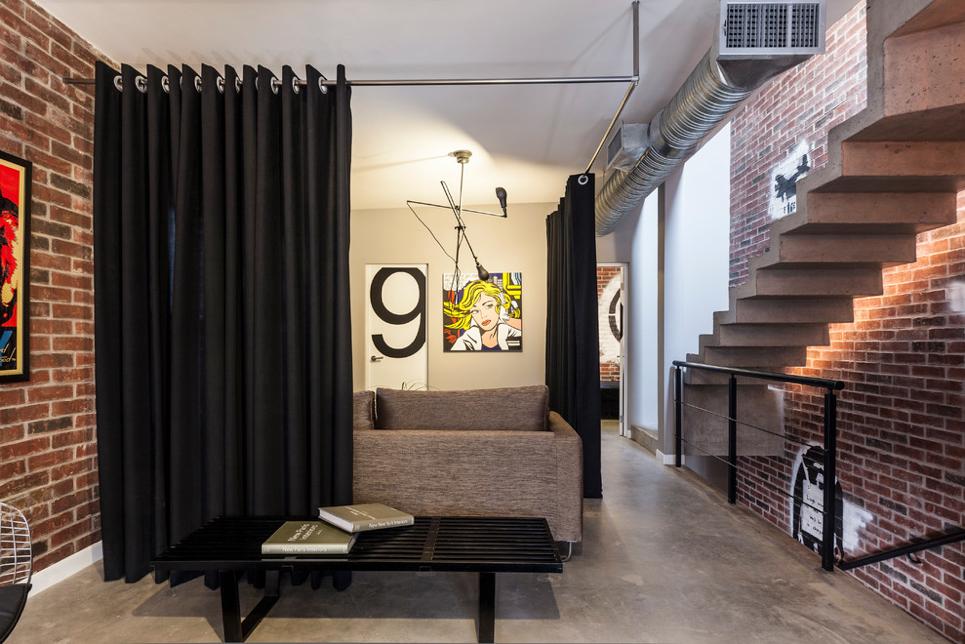 Sala moderna com divisória de ambiente de cortina preta.