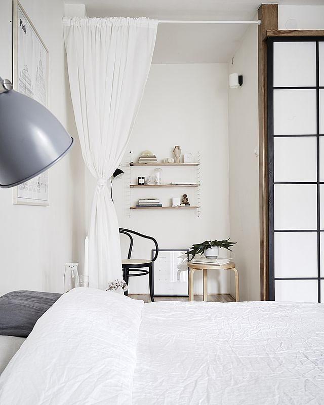 Quarto de casal minimalista com divisória de ambiente de cortina branca.