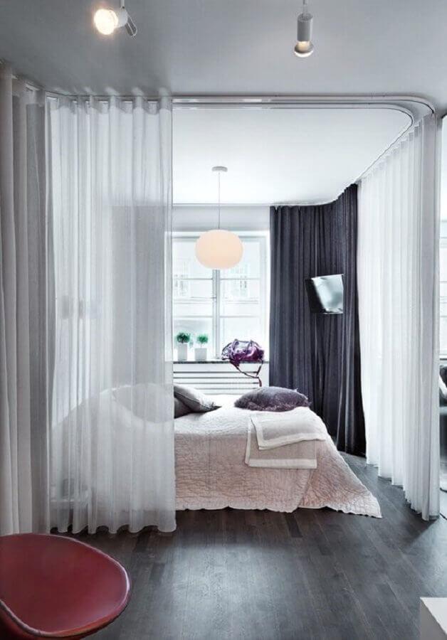 Quarto feminino com divisória de ambiente de cortinas brancas e pretas.