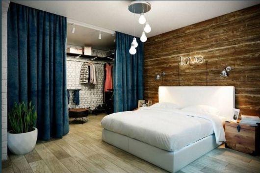 Closet com divisória de ambiente de cortina azul.