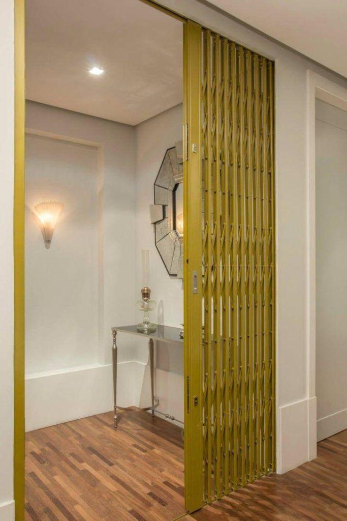 Sala decorada com divisória de ambiente com porta de ferro.