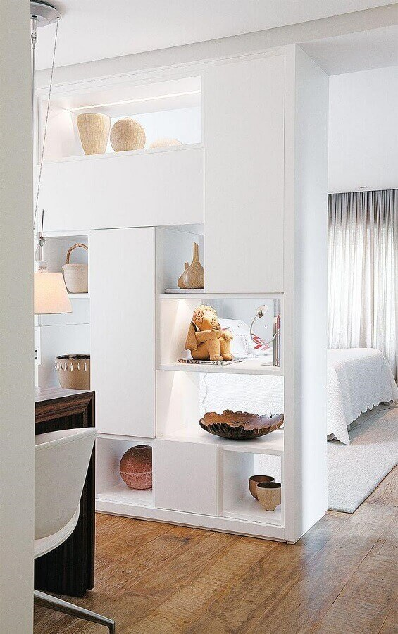 Quarto de casal decorado com divisória de ambiente armário.