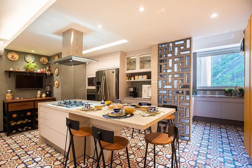 Cozinha com ilha com divisória de ambiente de cobogó.