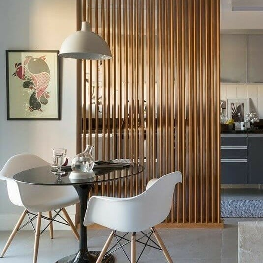 Cozinha pequena aberta com divisória de ambiente de madeira.