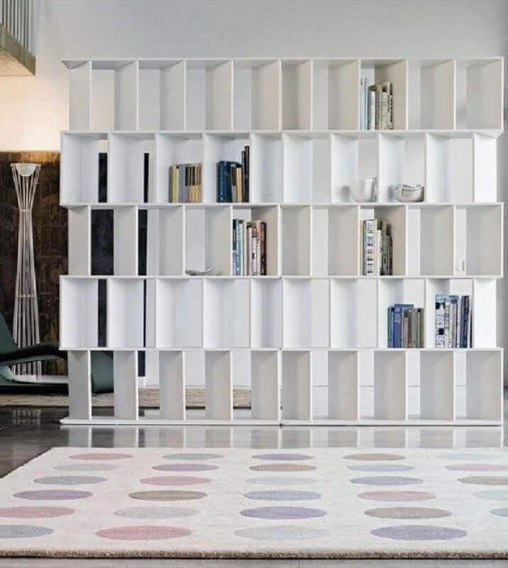 Sala decorada com estante que funciona como divisória de ambiente.