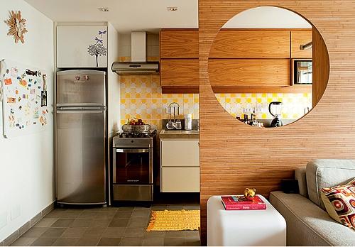 Cozinha americana decorada com painel de madeira.