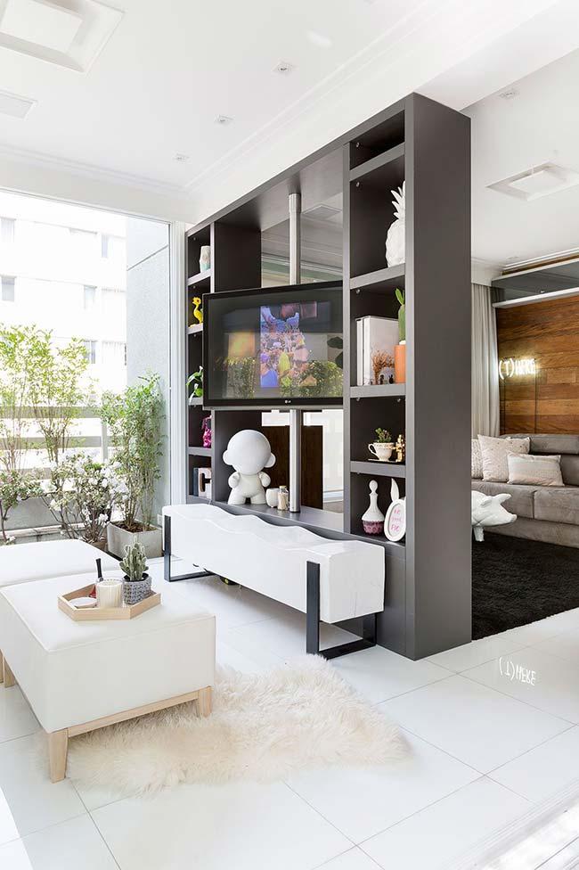 Apartamento pequeno decorado com divisória de ambiente com televisão rotativa.