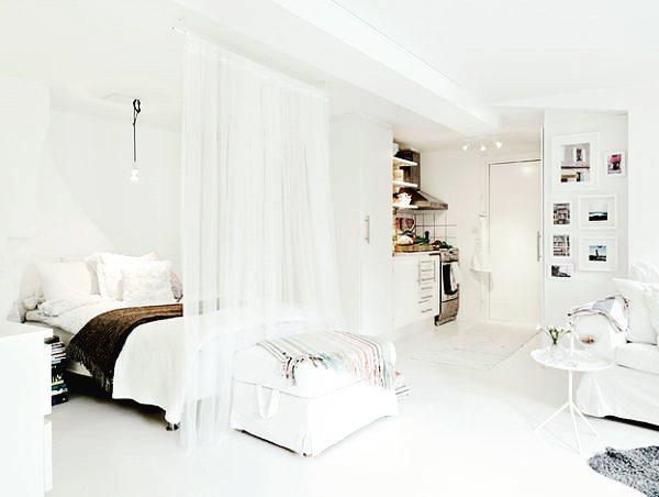 Loft minimalista com cortina que funciona como divisória de ambiente