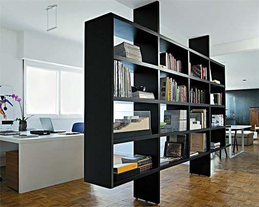 Escritório com estante de livros separando os ambientes.
