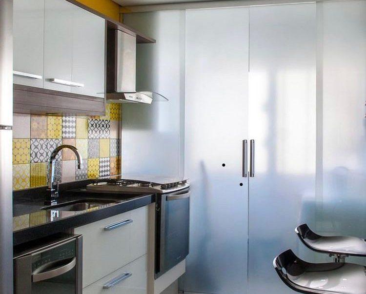 Cozinha pequeno e área de serviço separadas por porta de vidro.