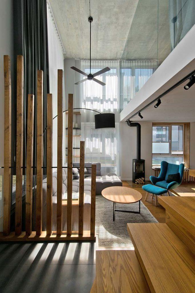 Sala moderna com divisória de ambiente de madeiras em ripas de tamanhos diferentes.