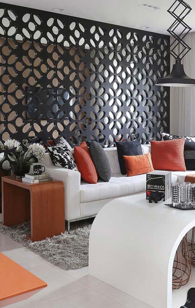 Sala decorada com divisória de ambiente vazada preta.