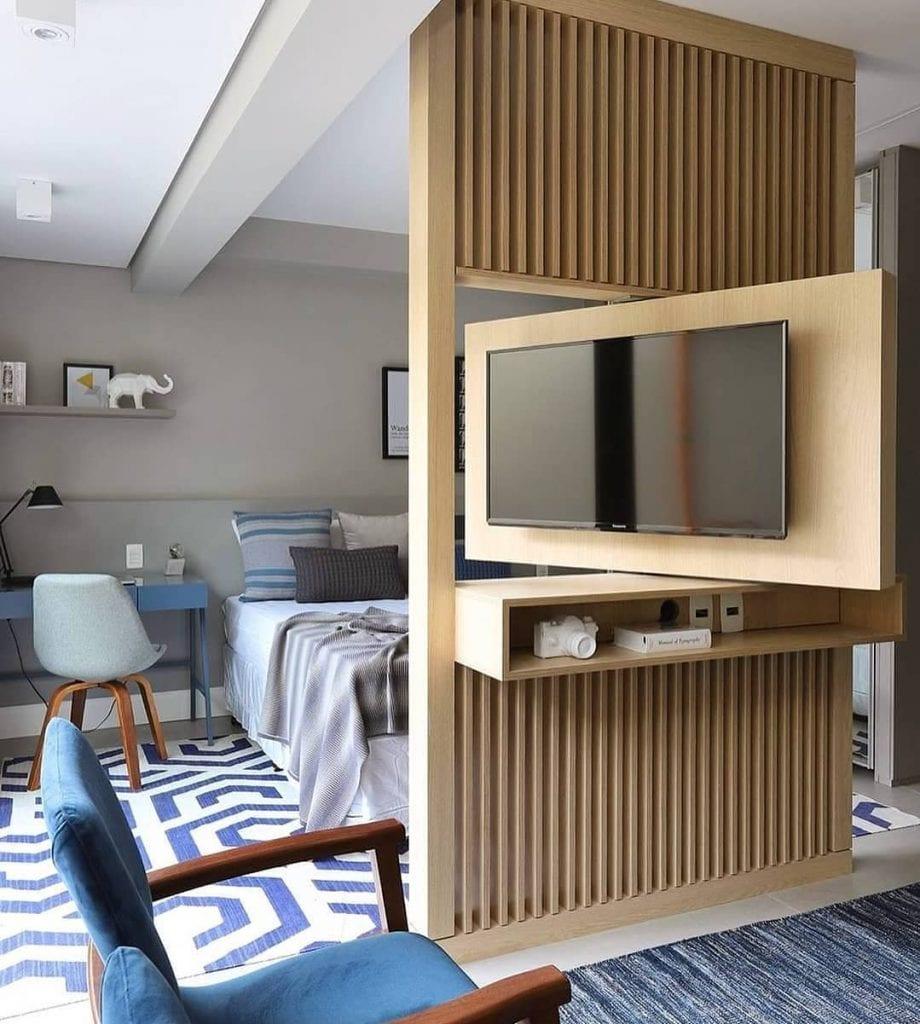 Apartamento pequeno com estante de MDF com tv giratória.