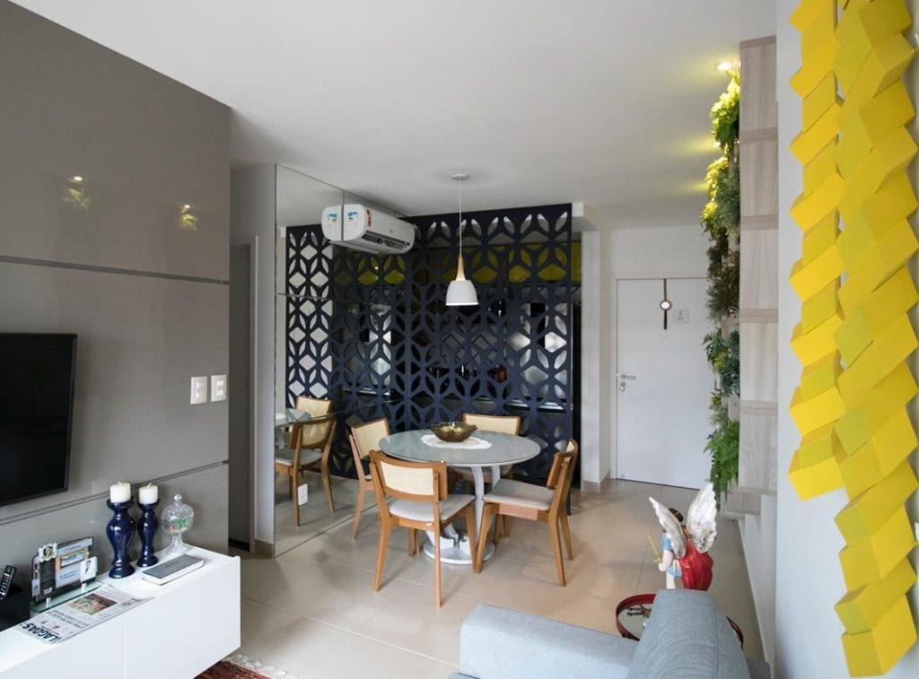 Sala separada da cozinha aberta por meio de divisória de ambiente vazada.