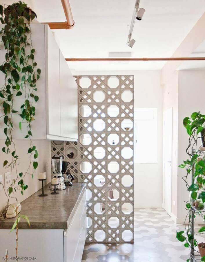 Cozinha pequena com parede de cobogó branco delicado.