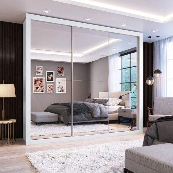 Quarto de casa cinza com guarda-roupa espelhado.